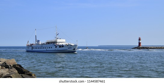 Warnemunde, Germany - June 8, 2018: A boat with tourists on deck is seen entering Warnemunde harbor, as it passes a red and white lighthouse and jetty
