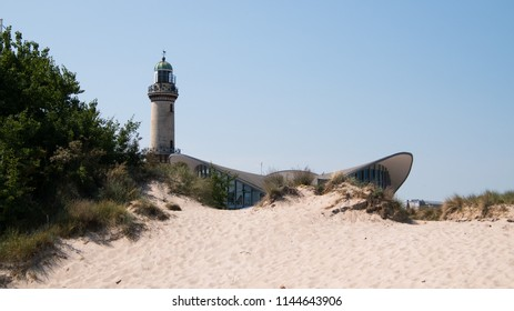 Warnemunde, Germany - June 8, 2018: Landmark lighthouse and shops in beach town of Warnemunde, Germany as seen from the beach on this date