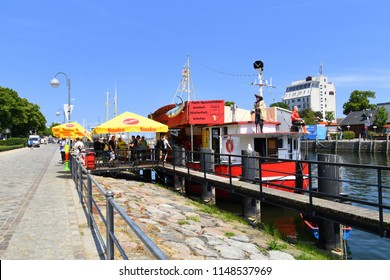 Warnemunde, Germany - June 8, 2018: Boat selling fried fish and smoked fish sandwiches docked on the canal in Warnemunde is serving customers