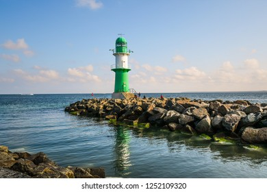 Warnemunde, Germany - September 15, 2018: Tourists relax on the rocks near the small green and white lighthouse at the mouth of Warnemunde Rostock Germany harbor as a ship cruises in the distance