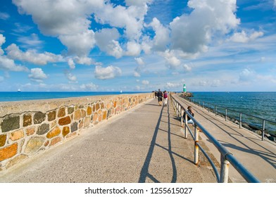 Warnemunde, Germany - September 15, 2018: Tourists walk the shoreline promenade near the small green and white lighthouse at Warnemunde Rostock Germany harbor as a ship cruises in the distance