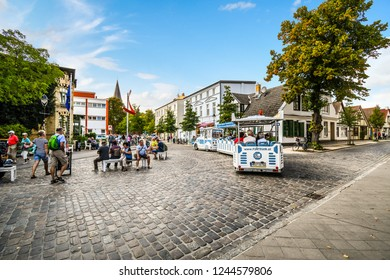 Warnemunde, Germany - September 4 2018: Tourists ride a tour tram through the streets of the coastal resort city of Warnemunde, Rostock, Germany.