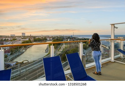 Warnemunde, Germany - September 4 2018: A woman on the upper deck of a cruise ship enjoys sunset over the coastal town, beach, Baltic Sea, Alter Strom canal and railway station in Warnemunde, Germany