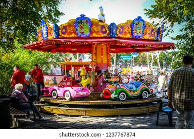 Warnemunde, Germany - September 6 2018: Carnival workers help a young child out of a small colorful carousel in the coastal town of Warnemunde Rostock, Germany.