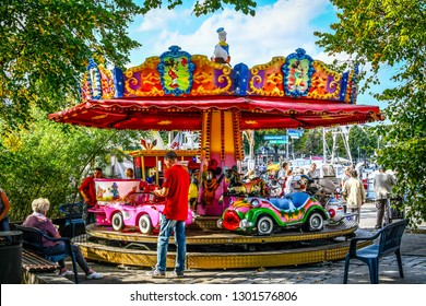 Warnemunde, Germany - September 6 2018: Carnival workers help a young child out of a small colorful carrousel as her grandmother waits in the coastal town of Warnemunde Rostock, Germany.
