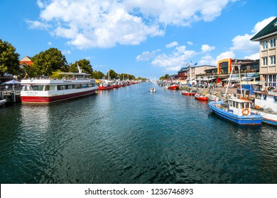 Warnemunde, Germany - September 7 2018: Shops and cafes line the Alter Strom canal at the cruise port in the resort town of Warnemunde, near Rostock on the northern coast of Germany.