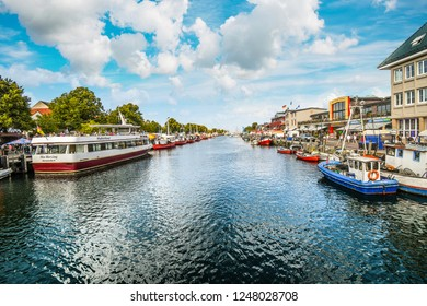 Warnemunde, Germany - September 7 2018: Shops, boats and cafes at the Alter Strom canal near the cruise port in the resort town of Warnemunde, near Rostock on the northern coast of Germany.