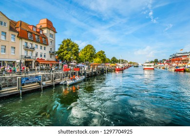 Warnemunde, Germany - September 7 2018: Tourists enjoy the shops, boats and cafes on the boardwalk at the Alter Strom canal in the resort town of Warnemunde, Rostock on the northern coast of Germany.