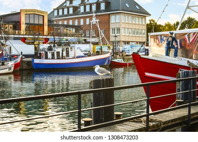 Warnemunde Rostock, Germany - September 3 2018: A single sea gull sits atop a wooden post in the Alter Strom canal in the picturesque harbor city of Warnemunde, Germany