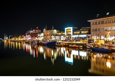 Warnemunde Rostock, Germany - September 4 2018: Late night illuminates the shops and cafes on the Alter Strom canal at the coastal city of Warnemunde, Germany, on the Baltic Sea.