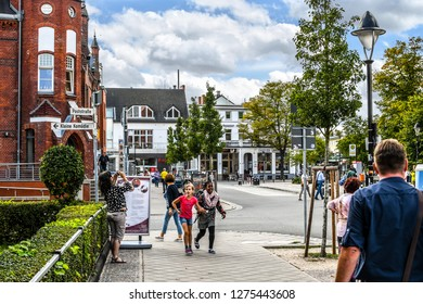 Warnemunde, Rostock Germany - September 4 2018: A young black girl and her young white friend walk hand in hand on a picturesque street in Warnemunde, Germany