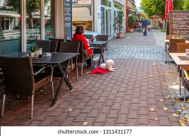 Warnemunde, Rostock Germany - September 4 2018: A woman sits alone at a table of a sidewalk cafe with her small, white poodle breed dog next to her as tourists and Germans shop in Warnemunde Germany
