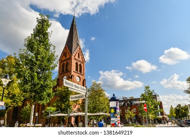 Warnemunde, Rostock Germany - September 4 2018: The neo-gothic Warnemunde Church tower rises above the coastal town of Rostock, Germany, as tourists and Germans dine on the patio in the open square.
