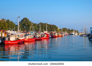Warnemunde Rostock Germany - September 4 2019: A line of red tourist and fishing boats line the Alter Strom Canal in the coastal resort of Warnemunde on the Baltic Sea.                                - Shutterstock ID 2044620401