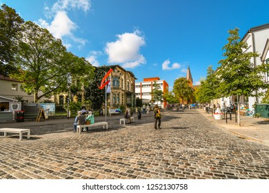 Warnemunde Rostock, Germany - September 5 2018: Tourists and local Germans walk through the main square intersection of the coastal resort city of Warnemunde, with the spire of the church in view.