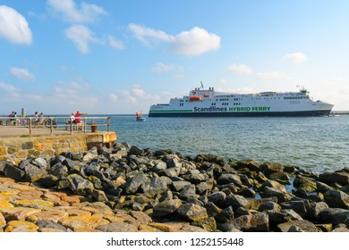 Warnemunde Rostock, Germany - September 5 2018: Tourists relax on the boardwalk at the coast of the Baltic Sea as they watch ferries cruise out of the port of Warnemunde Rostock, Germany