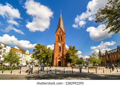 Warnemunde, Rostock, Germany - September 5 2018: The neogothic Warnemunde Church tower rises above the coastal town of Rostock, Germany, as tourists and Germans dine on the patio in the open square.