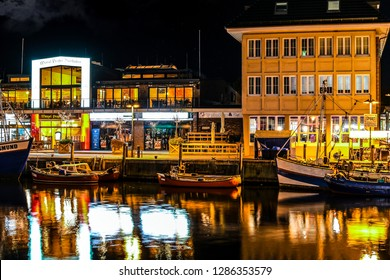 Warnemunde Rostock, Germany - September 5 2018: Illuminated shops and cafes in the evening as boats dock along the Alter Strom canal in the Baltic city of Warnemunde, Germany.