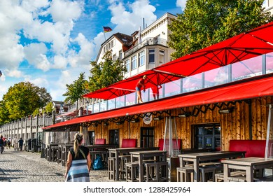 Warnemunde, Rostock Germany - September 5 2018: A woman stands on a roof and cleans the glass on the upper level of a sidewalk cafe on a summer day in the coastal resort of Warnemunde, Germany