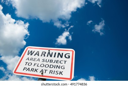 warning area subject to flooding sign against a blue sky