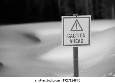 warning caution ahead sign in black and white before frozen pond thin ice in winter with sunny warmer weather fresh  white snow horizontal format room for type