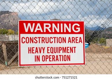 Warning construction area sign posted on a chain link fence in a construction zone