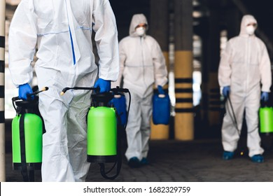 Warning, coronavirus disinfection. Men in virus protective suits carrying spray bottles with chemicals, blurred background