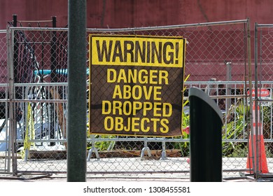 Warning Danger Above Dropped Objects large brown and yellow vinyl sign on chain length safety and security fence around a construction site in downtown Fort Lauderdale Broward County Florida.