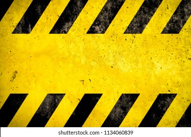Warning danger background with yellow and black stripes painted over yellow concrete wall facade texture and empty space for text message in the middle. Concept image for caution, danger and hazard.