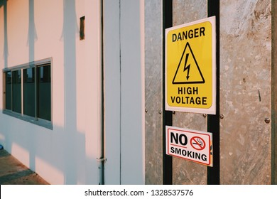 Warning danger high voltage sign and no smoking label on steel pipe cover with sunlight and electric pole's shadow on surface of white wall, sign and symbol with safety concept