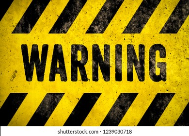 WARNING danger sign word text as stencil with yellow and black stripes painted over concrete wall cement texture background. Concept image for caution, dangerous area and hazard.