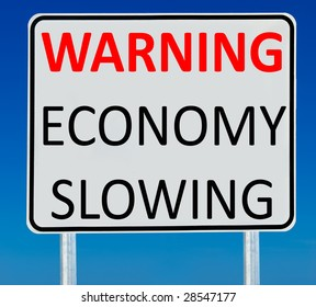 "A ""Warning Economy Slowing"" sign isolated on a blue graduated sky."