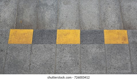 Warning of footpath painted black and yellow.