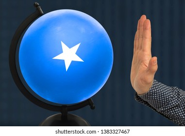 The warning gesture of a man's hand refers to a globe with a colored national state flag somali