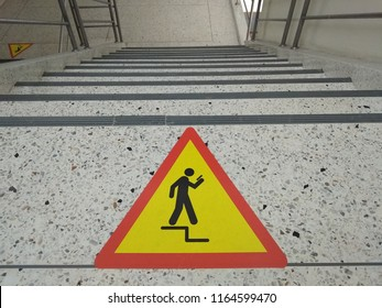 Warning icon floor leveling, mind your step. Walk down the stairs to be careful. Catch the railing at the stairs. Don't use smartphone temporary.