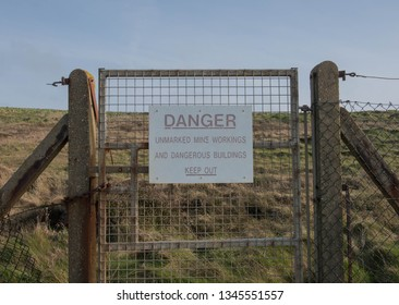 Warning to Keep Out and Danger Sign for Unmarked Mine Workings and Dangerous Buildings Attached to a Metal Gate on the South West Coast Path at Portreath Airfield in Rural Devon, England, UK