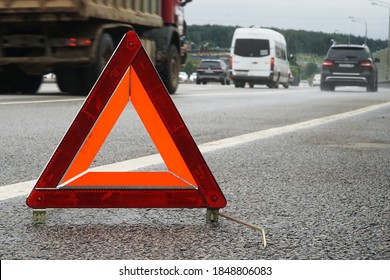 A warning road sign for an emergency stop stands on the asphalt against the background of moving cars.