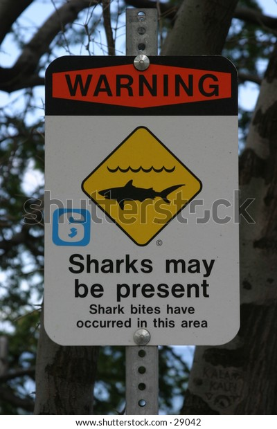 """a """"Warning sharks may be present sign"""" letting surfers and swimmers know if they are not careful they may become a sharks lunch (like a butterfly to a preying manits) showing the circle of life"""