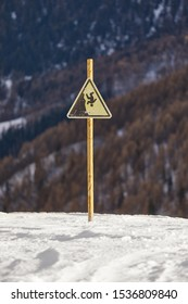 Warning sign about falling of a cliff in snowy mountains