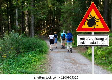 """Warning sign """"beware of ticks"""" in infested area in the green woods with hikers"""