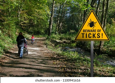 """Warning sign """"beware of ticks"""" in infested area in a park with walking family"""