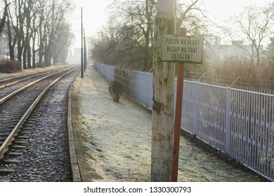 Warning sign, beware train. Do not enter. In background of tracks and cars. Morning light and frost.
