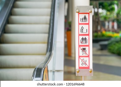 warning sign board in front of escalator with blurred background