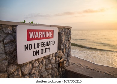 warning sign board 'no lifeguard on duty' on rock wall at beach with sea and sky background in sunrise and copy space