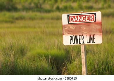 Warning sign concerning power line in green field