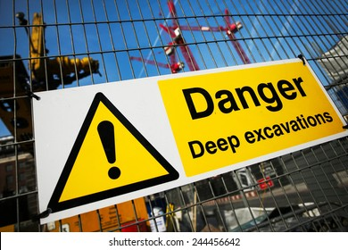 warning sign at construction site, multiple cranes working in the background