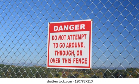 Warning Sign: Danger, Do Not Attempt to Go Around, Through, Or Over the Fence Posted on Chain Link Fence