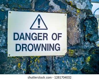 Warning sign danger of drowning on a stone wall.