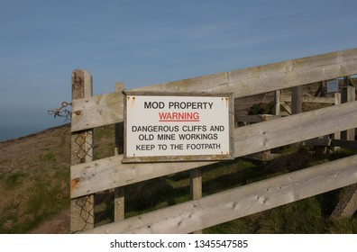 Warning Sign for Dangerous Cliffs and Old Mining Works Attached to a Fence by the Disused MOD Property of Portreath Airfield on the South West Coast Path in Rural Cornwall, England, UK