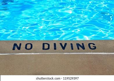 warning sign at edge of swimming pool